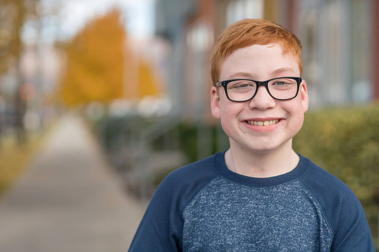 Smiling boy with glasses and red hair