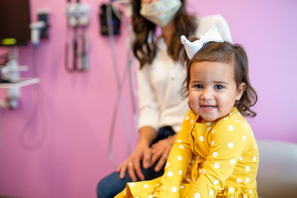 Little girl in yellow shirt in exam room with mom wearing mask in the background